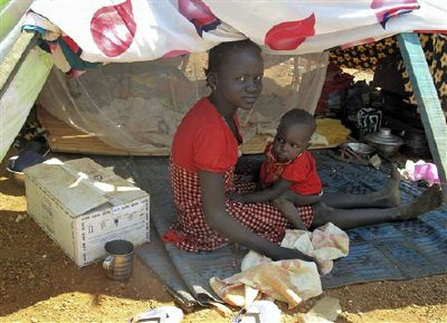 A woman and child sit in the shade in the UN compound where they have sought shelter in Juba, South Sudan, from ethnic fighting. Photo: AP / World Food Programme