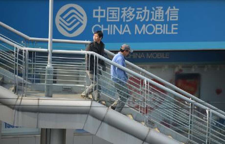 Two men walk past a China Mobile sign on a street in Shanghai. China's credit market is in a crunch and could affect the whole world. Photo: AFP/Getty Images / 2013 AFP