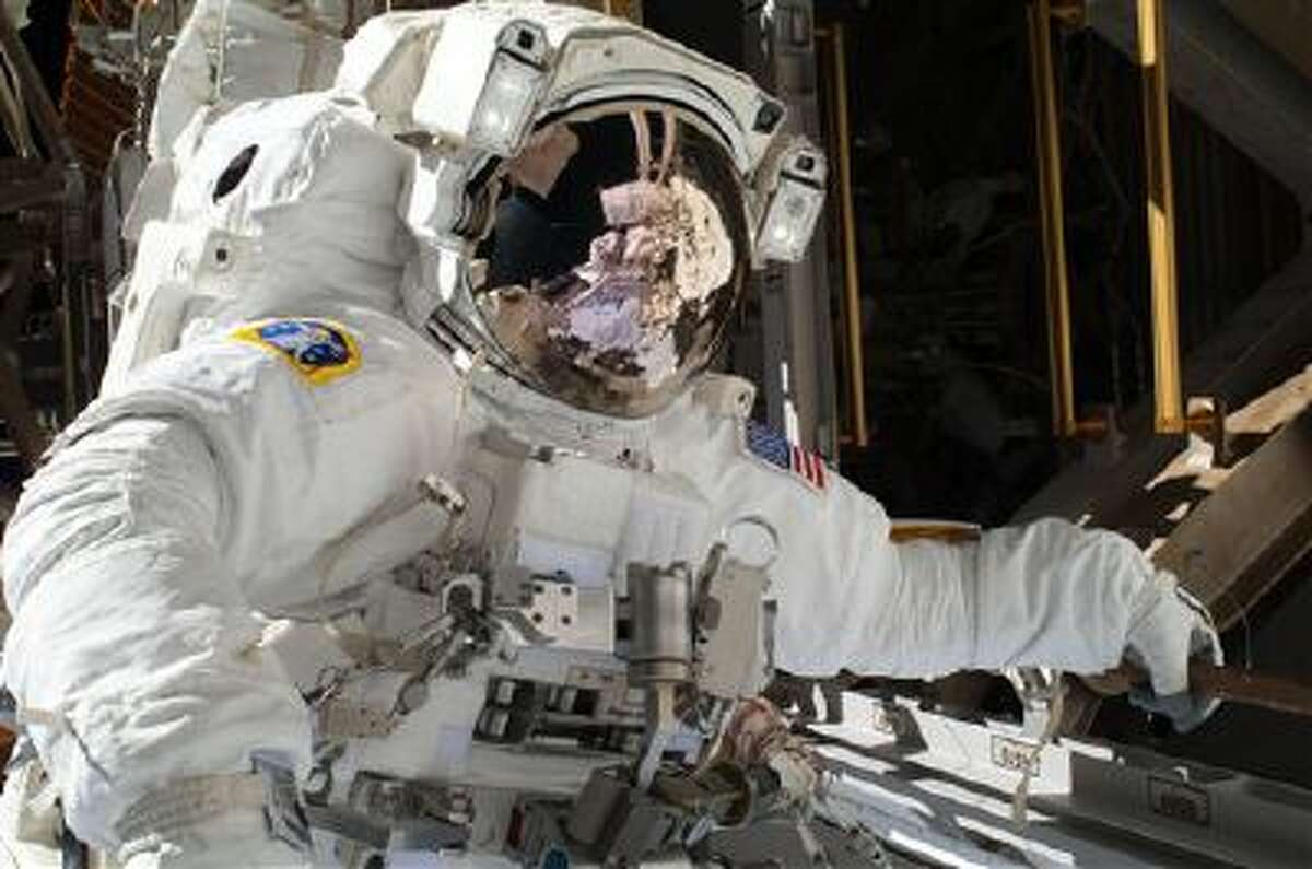 In this Saturday, NASA astronaut Michael Hopkins work to repair an external cooling line on the International Space Station.