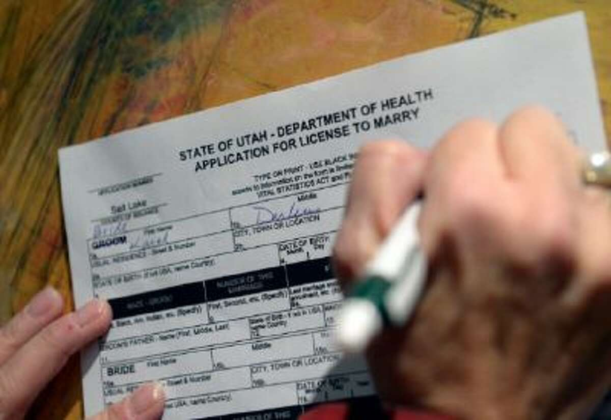 A woman seeking a same-sex marriage fills out the license application on Friday, Dec. 20, in Salt Lake City.