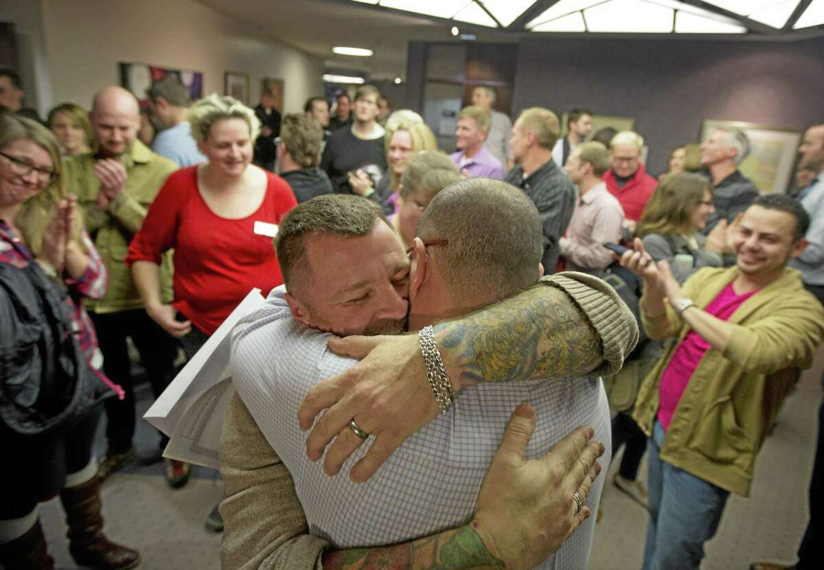 In this Dec. 20, 2013 file photo, Chris Serrano, left, and Clifton Webb embrace after being married, as people wait in line to get licenses outside of the marriage division of the Salt Lake County Clerk's Office in Salt Lake City. A federal judge on Monday, is set to consider a request from the state of Utah to block gay weddings that have been taking place since Friday when the state's same-sex marriage ban was overturned. AP Photo/Kim Raff