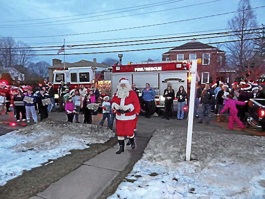 Santa, along with carolers from Middletown High, delivered gifts to the adopted families for the holidays. Photo: Submitted Photo.