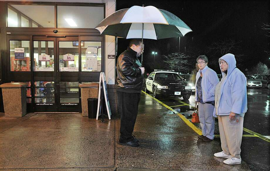 A Stop & Shop employee, at left informs shoppers that the store is temporarily closed Monday night and will re-open shortly. Middletown Police Department closed the grocery store due to a bomb threat made at 3 p.m and the store re-opened at approximately 5:30 p.m.  Catherine Avalone - The Middletown Press Photo: Journal Register Co. / TheMiddletownPress