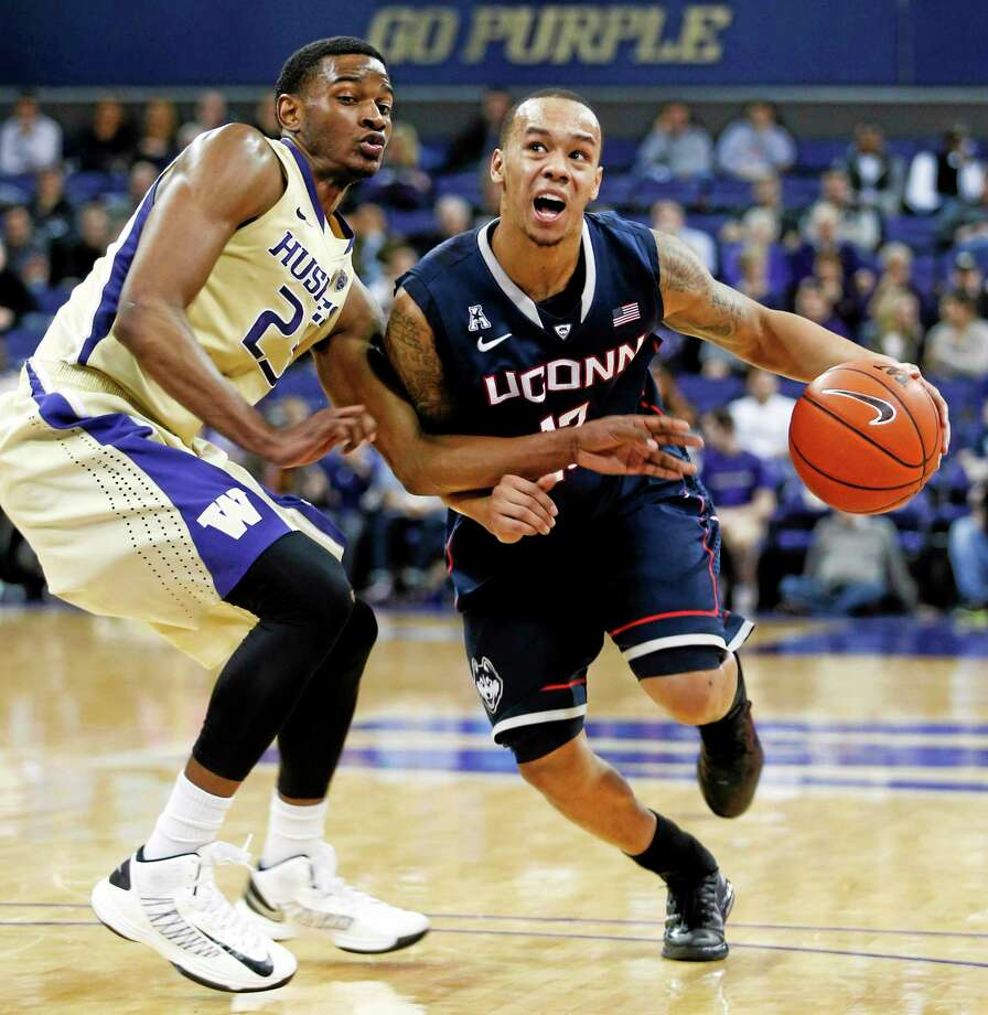 UConn's Shabazz Napier, right, drives to the basket against Washington's C.J. Wilcox during Sunday's game. Photo: John Froschauer — The Associated Press  / FR74207 AP