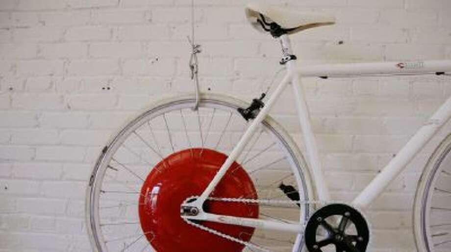 In this Thursday, Dec. 12, 2013 photo, a bicycle fitted with a prototype of the Copenhagen Wheel, the red disk, a human/electric hybrid bicycle engine, hangs on a wall at Superpedestrian, the hybrid engine's manufacturer in Cambridge, Mass.