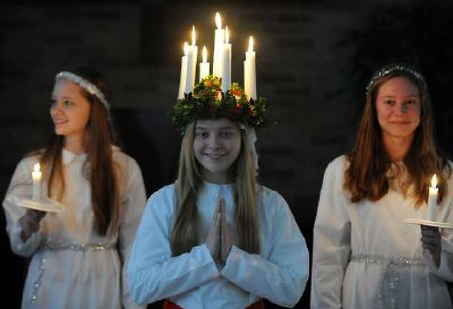 Julia Sandberg, 14, as Santa Lucia, center, Hedvig Unander-Scharin , 16, right, and Kate Reis, 14, left, participate in a Lucia ceremony held by members of the Swedish School for Language in Washington. Dating back to the14th century, the Swedish ceremony is a way to cop with evil spirits.