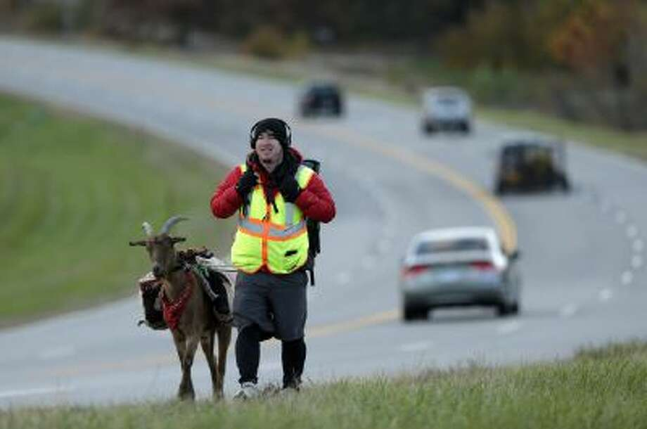 In this Wednesday, Nov. 6, 2013 photo, Steven Wescott walks with his goat, LeeRoy Brown, along a street in Lenexa, Kan.
