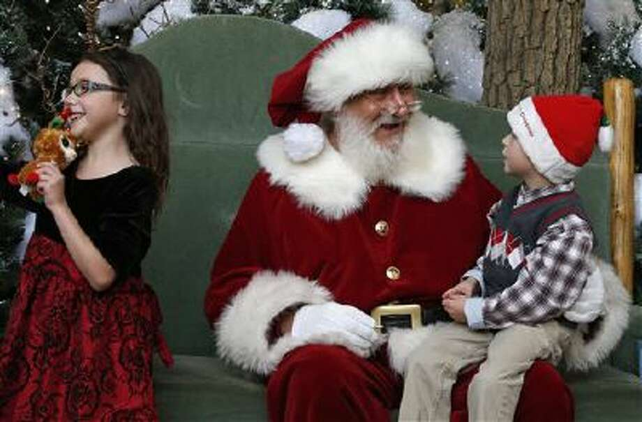 Santa chats with Asher Powell, age 6, while Asher's sister Alexis smiles Wednesday during a visit to Santa's Wonderland House inside Flatirons Crossing Mall in Broomfield, Colo. Photo: AP / AP