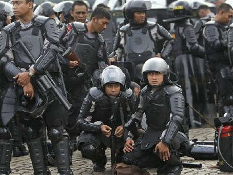 Indonesian police officers in riot gear take a break Friday during a show of force ahead of Christmas celebrations in Jakarta, Indonesia. Since the Bali bombings in 2002, the world's largest Muslim country has been battling terrorists. Photo: AP / AP