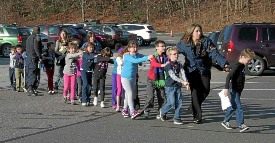 FILE - In this Dec. 14, 2012 file photo provided by the Newtown Bee, Connecticut State Police lead a line of children from the Sandy Hook Elementary School in Newtown, Conn., where gunman Adam Lanza opened fire, killing 26 people, including 20 children. (AP Photo/Newtown Bee, Shannon Hicks, File) MANDATORY CREDIT: NEWTOWN BEE, SHANNON HICKS Photo: AP / Newtown Bee