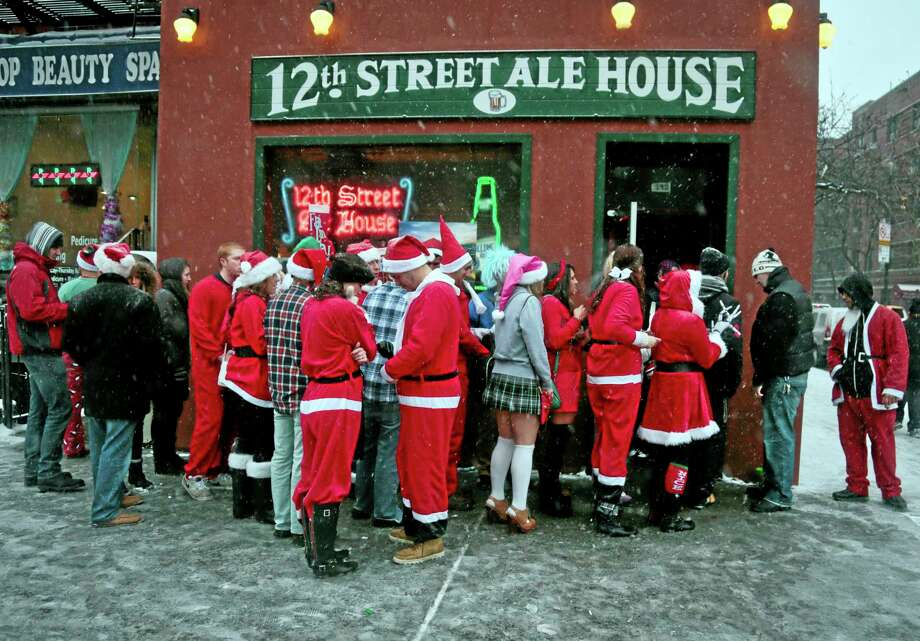 Santacon participants lineup outside a lower eastside bar on Saturday, Dec. 14, 2013 in New York.  Thousands of red-suited revelers spread out through the city's bars and snowy streets amid criticism that the event has become too rowdy. (AP Photo/Bebeto Matthews) Photo: AP / AP