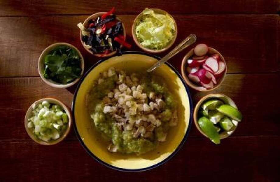 Posole is surrounded with toppings, clockwise from bottom left: green onions, cilantro, tortilla chips, cabbage, radishes and limes.
