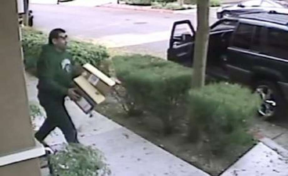 A frame of the video shows a suspect who appears to be male wearing a green sweatshirt. He exits a green Jeep Cherokee with chrome wheels and retrieves two packages that were delivered to a South San Jose townhouse.