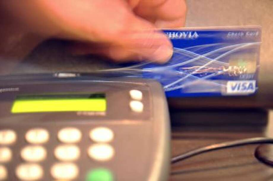 A credit card is swiped. Photo: AFP/Getty Images / 2010 AFP