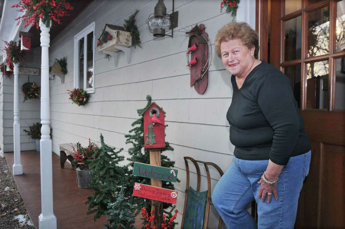 Barbara Fountain on the decorated porch of her Cromwell home Friday afternoon. In two weeks, Fountain will put all the Christmas decor away.