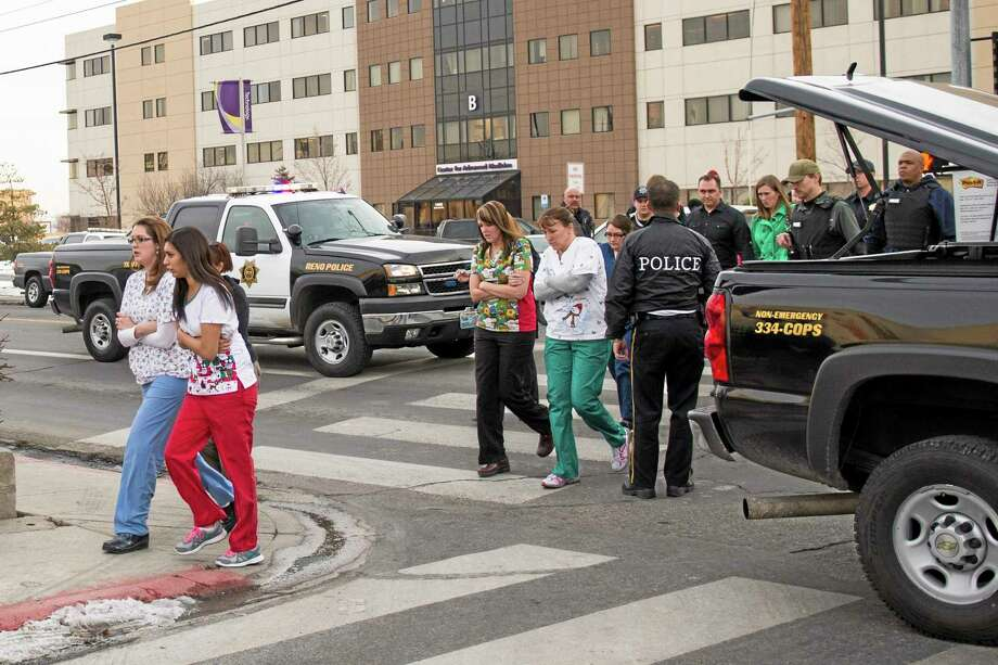 Officers escort witnesses to a bus at the Renown Regional Medical Center after a lone gunman shot and injured four people before killing himself , Tuesday, Dec. 17, 2013 in Reno, Nev. (AP Photo/Scott Sady) Photo: AP / FR78397 AP