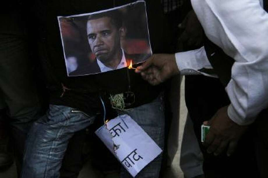 Indian Muslims burns an effigy of U.S. President Barack Obama as he and others protest against the alleged mistreatment of New York based Indian diplomat Devyani Khobragade on Thursday, Dec. 19.