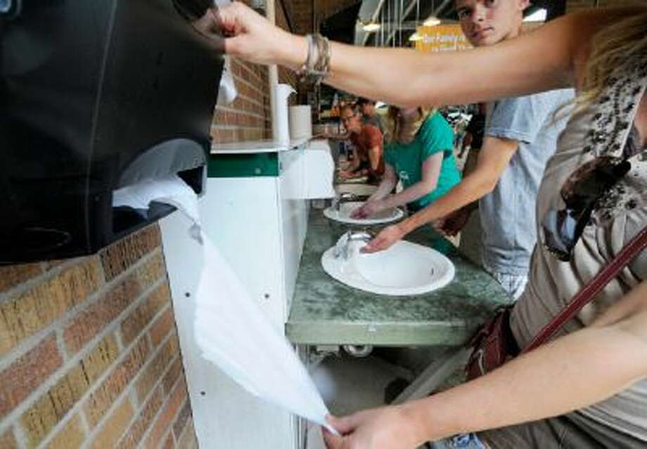 Visitors to the swine and sheep building at the Minnesota State Fair wash their hands after visiting the building in keeping with advice from health officials.