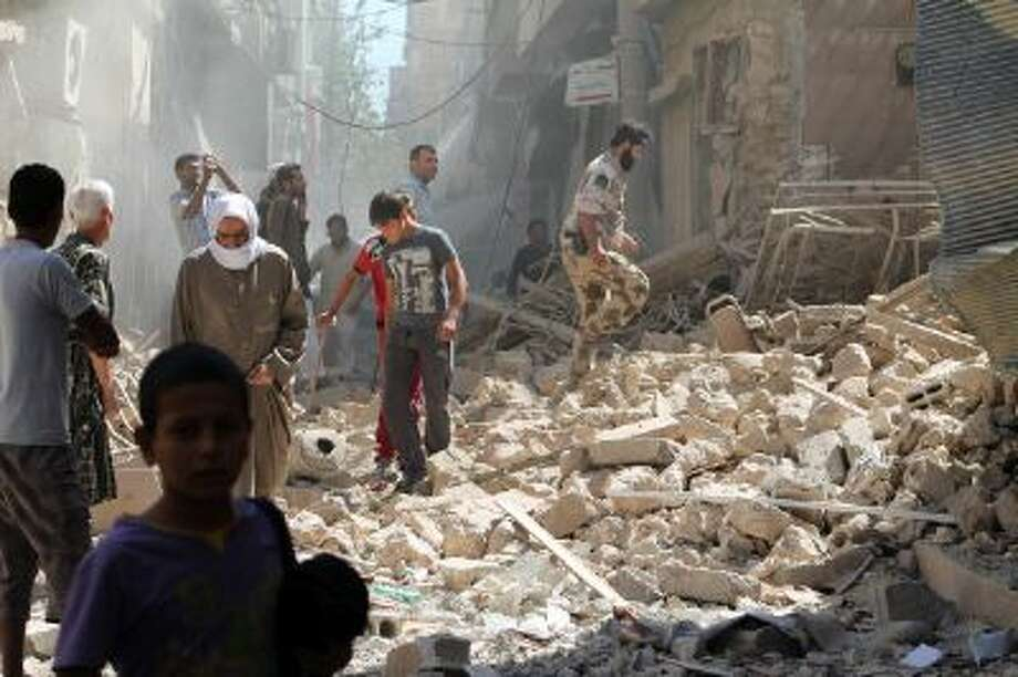 Residents of Syria's eastern town of Deir Ezzor walk past the debris of a building reportedly hit by a missile on September 26. The Syrian Observatory for Human Rights said on September 14, that there was fighting between rebels and units of the jihadist Islamic State of Iraq and the Levant (ISIS) in Albu Kamal, with five people killed. Photo: AFP/Getty Images / 2013 AFP