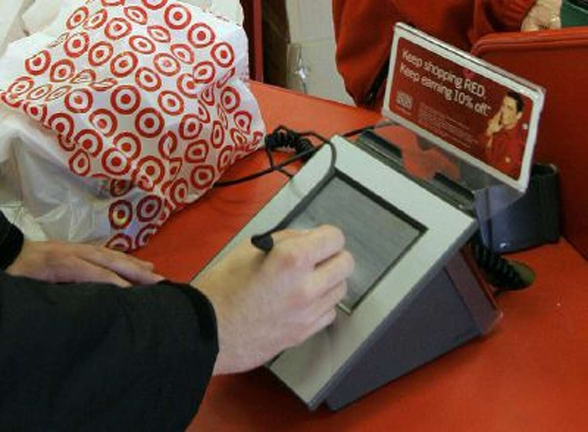 A customer signs his credit card receipt at a Target store in Tallahassee, Fla., in January 2008.