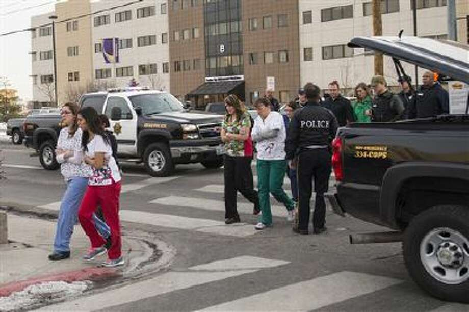 Officers escort witnesses to a bus at the Renown Regional Medical Center in Reno, Nev., after a lone gunman opened fire before killing himself on Dec. 17, 2013. Photo: AP / FR78397 AP