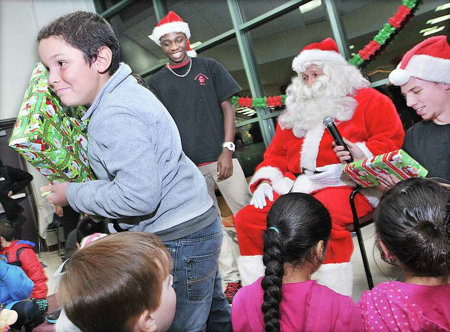 Javon Rivera, 8, smiles after receiving his gift from Santa and the elves, seniors Kwaby Asante, at left and Liam Kenney at the Holiday Party Thursday evening sponsored by the Cromwell Student Council and Cromwell Youth Services. Rivera was very happy find a Wood Building Set. Photo: Catherine Avalone — The Middletown Press  / TheMiddletownPress