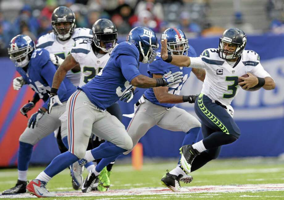 Seahawks quarterback Russell Wilson stiff-arms New York Giants defensive end Justin Tuck (91) during the second half of Seattle's 23-0 win on Sunday in East Rutherford, N.J. Photo: Kathy Willens — The Associated Press  / AP