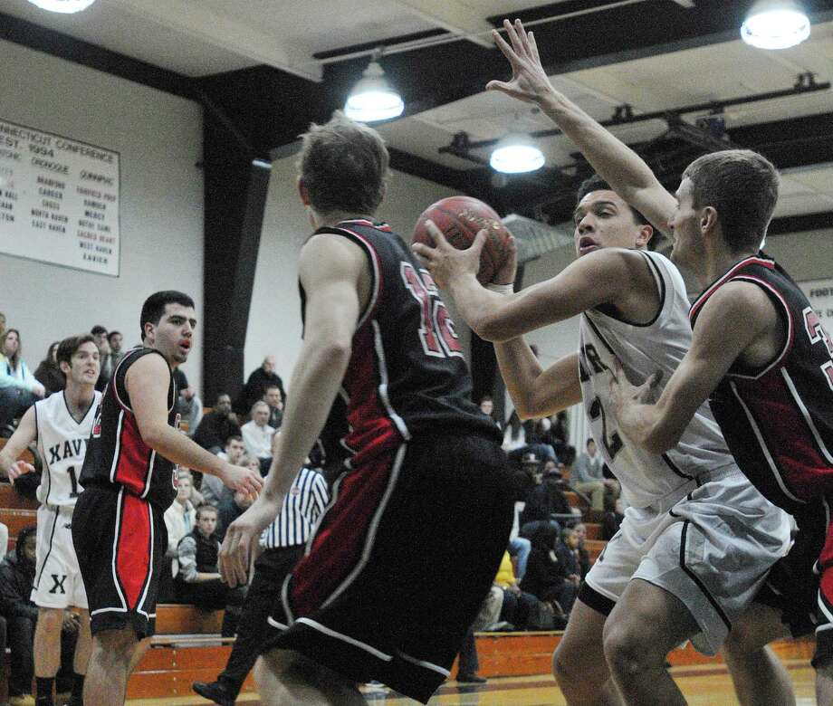 Xavier junior center Kaleb Lutton looks to make a pass as Cheshire's Reid Duglenski (12) and Tyler Post (30) defend Monday night in Middletown. Xavier won 45-41. Photo: Catherine Avalone — The Middletown Press  / TheMiddletownPress