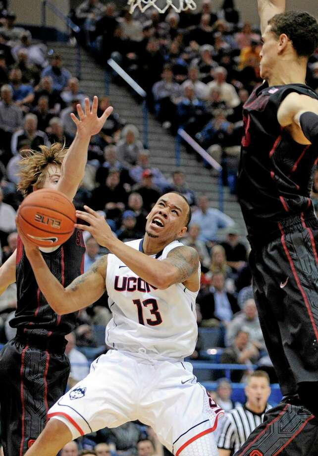 UConn's Shabazz Napier (13) tries to split a pair of Stanford defenders during the second half of Wednesday's game in Hartford. UConn fell 53-51. Photo: Fred Beckham  — The Associated Press  / FR153656 AP
