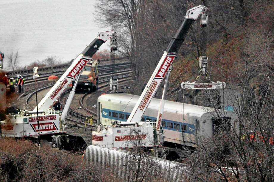 """Cranes lift a derailed Metro-North train car, Monday, Dec. 2, 2013, in the Bronx borough of New York. Federal authorities began righting the cars Monday morning as they started an exhaustive investigation into what caused a New York City commuter train rounding a riverside curve to derail, killing four people and injuring more than 60 others. A second """"event recorder"""" retrieved from the train may provide information on the speed of the train, how the brakes were applied, and the throttle setting, a member of the National Transportation Safety Board said Monday.  (AP Photo/Mark Lennihan) Photo: AP / AP"""