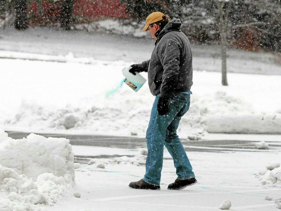 Erik Johnson, Branford High School head custodian, sprinkles snow melt along walk ways at Branford High School to keep the entrances to the school clear Tuesday morning. Photo: Peter Hvizdak — New Haven Register  / ©Peter Hvizdak /  New Haven Register