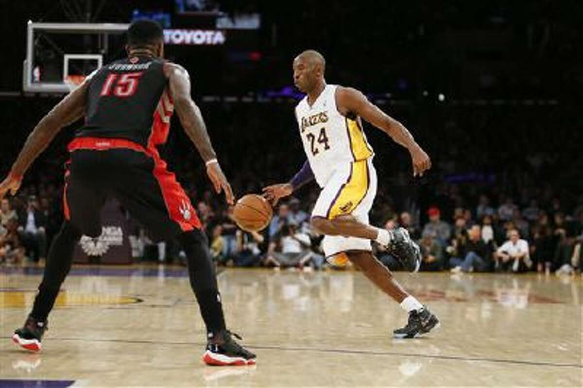 Los Angeles Lakers' Kobe Bryant dribbles the ball as Toronto Raptors' Amir Johnson, left, defends during the first half of an NBA basketball game in Los Angeles, Sunday, Dec. 8, 2013.