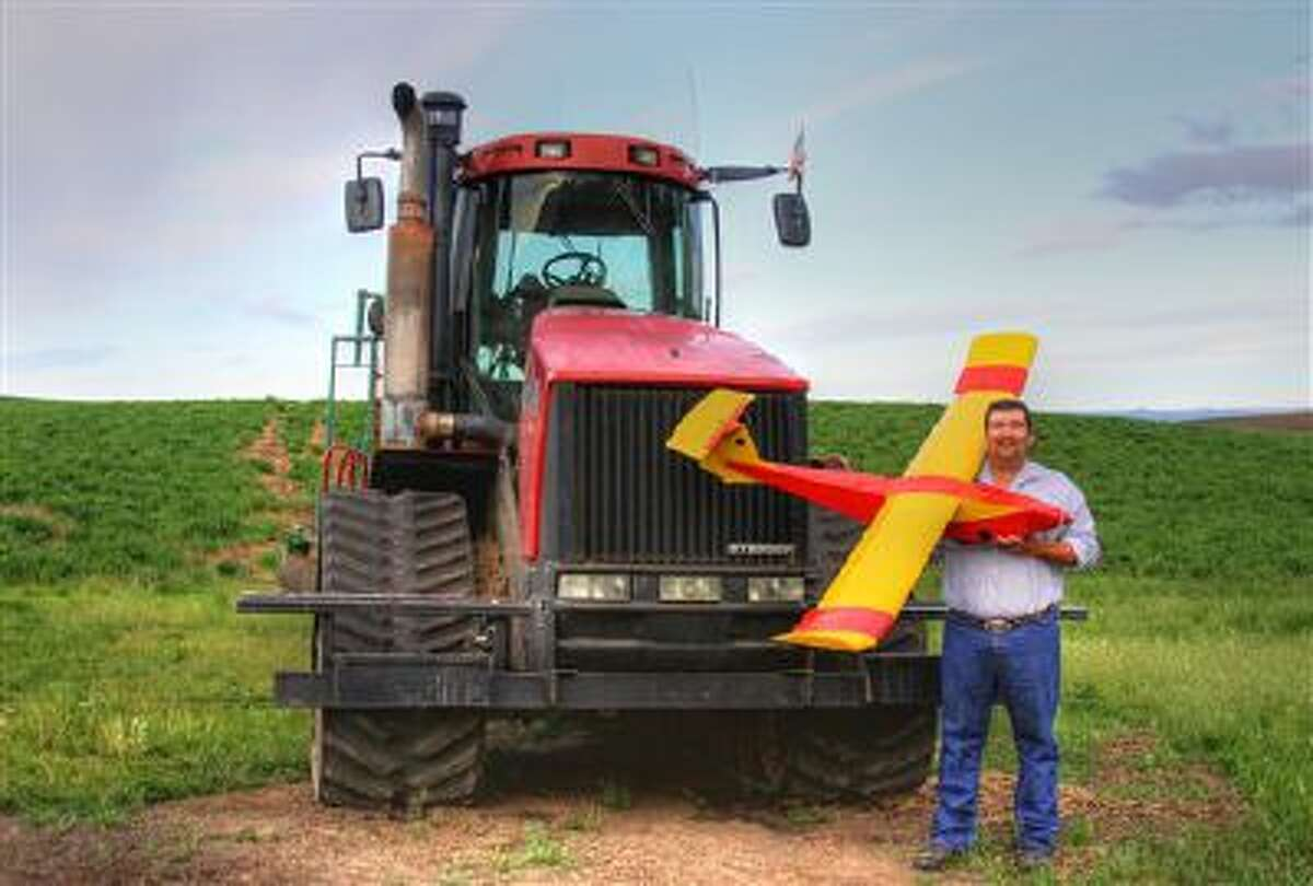 Farmer Robert Blair stands in front of his tractor holding an unmanned aircraft that he built in Kendrick, Idaho. Blair uses the home-made drone equipped with up to four cameras to