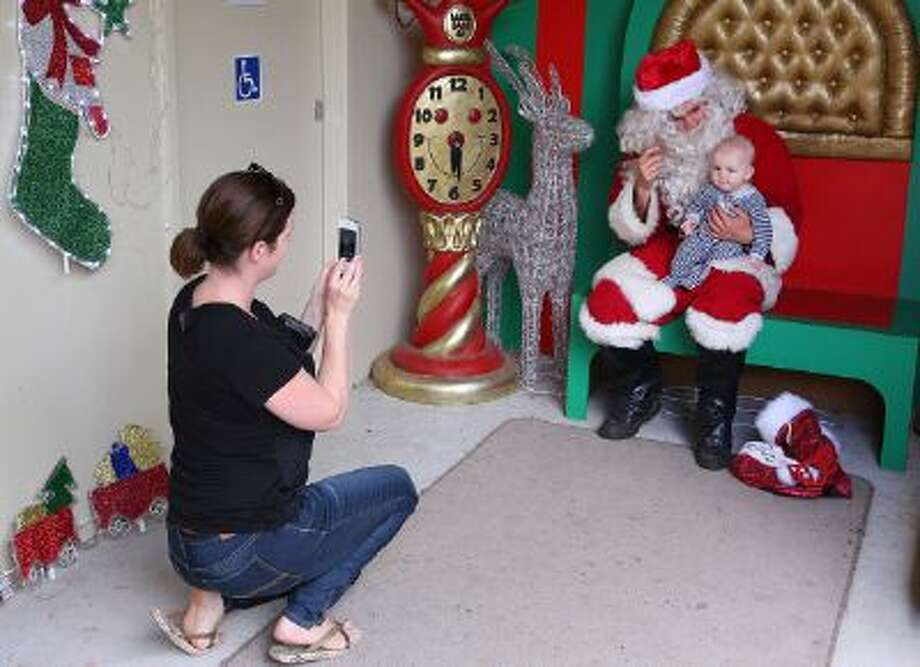 A mother captures her baby with Santa Claus during a photo session on December 16, 2013 in Melbourne, Australia. Photo: Getty Images / 2013 Getty Images