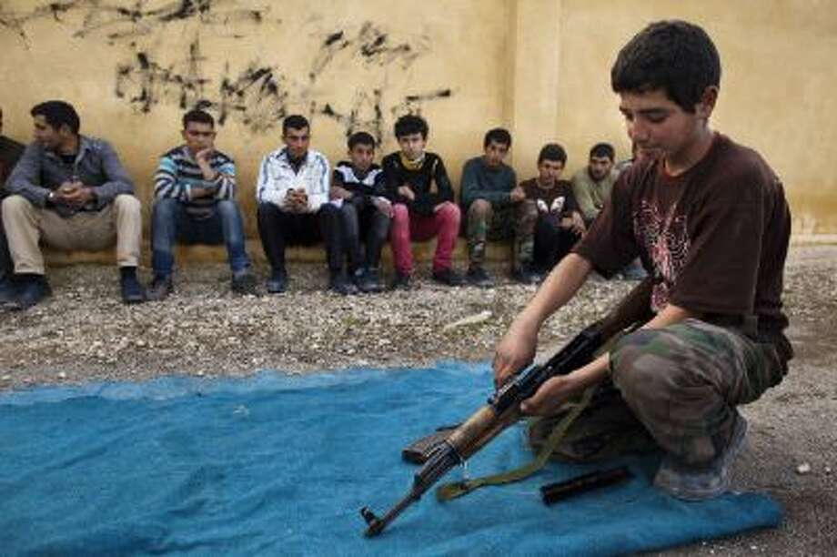 """A Syrian youth holds an AK-47 assault rifles as he takes part in a military training in January 2013 at a former school turned into a """"military academy"""" in Tlaleen in the northern Syria's Aleppo province. Factions on all sides of the conflict have been accused of using child soldiers. Photo: AFP/Getty Images / 2013 AFP"""