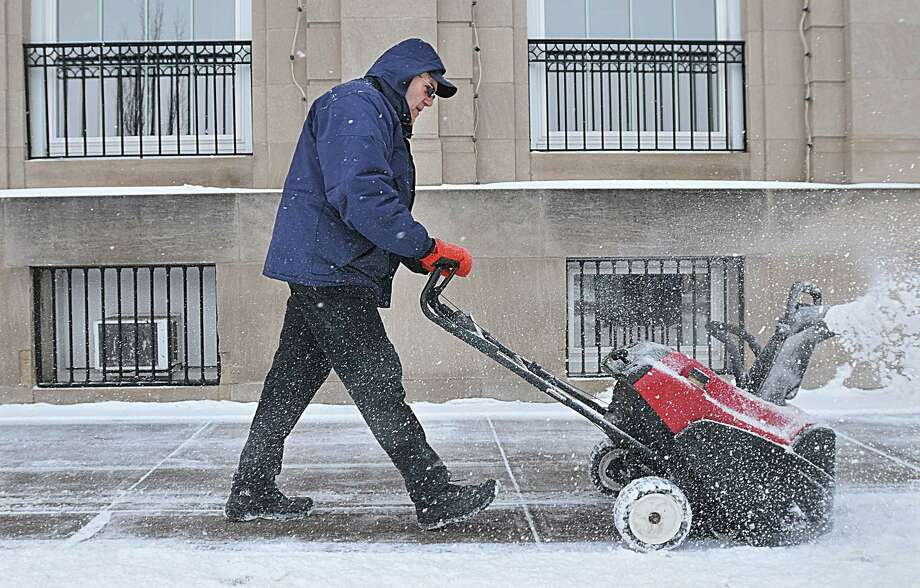 Baltic resident Ed Bastien, a maintenance worker at Liberty Bank on Main Street in Middletown, uses a snowblower to clear the sidewalk at the bank Tuesday afternoon. Photo: Catherine Avalone — The Middletown Press  / TheMiddletownPress
