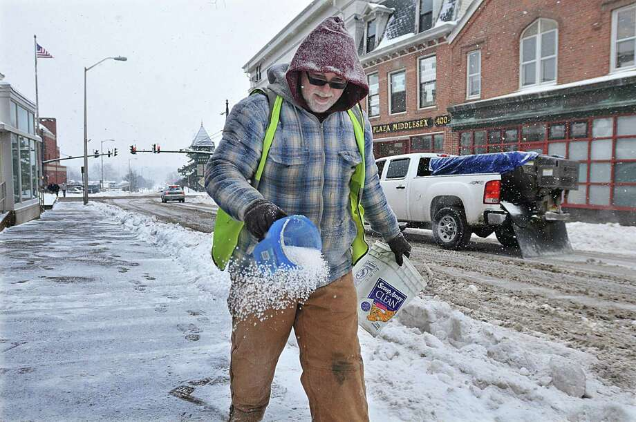 """Lifelong Middletown resident Darren Bula, employed by Xenelis Construction in Middlefield sprinkles salt on the sidewalk on College Street at Citizen Bank in Middletown Tuesday. Bula said, """"We take care of all the Citizen Bank properties. Sometimes I plow, I do whatever Xenelis needs me to do."""" Photo: Journal Register Co. / TheMiddletownPress"""