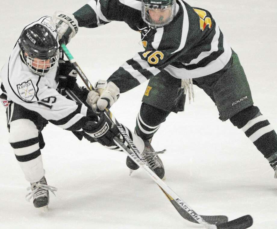 Xavier junior forward Bryan Stanton (19) battles Hamden sophomore forward Tyler Carangelo Wednesday night at the Spurrier-Snyder Rink at Wesleyan's Freeman Athletic Center. The game ended in a 2-2 tie in overtime. Photo: Catherine Avalone — The Middletown Press