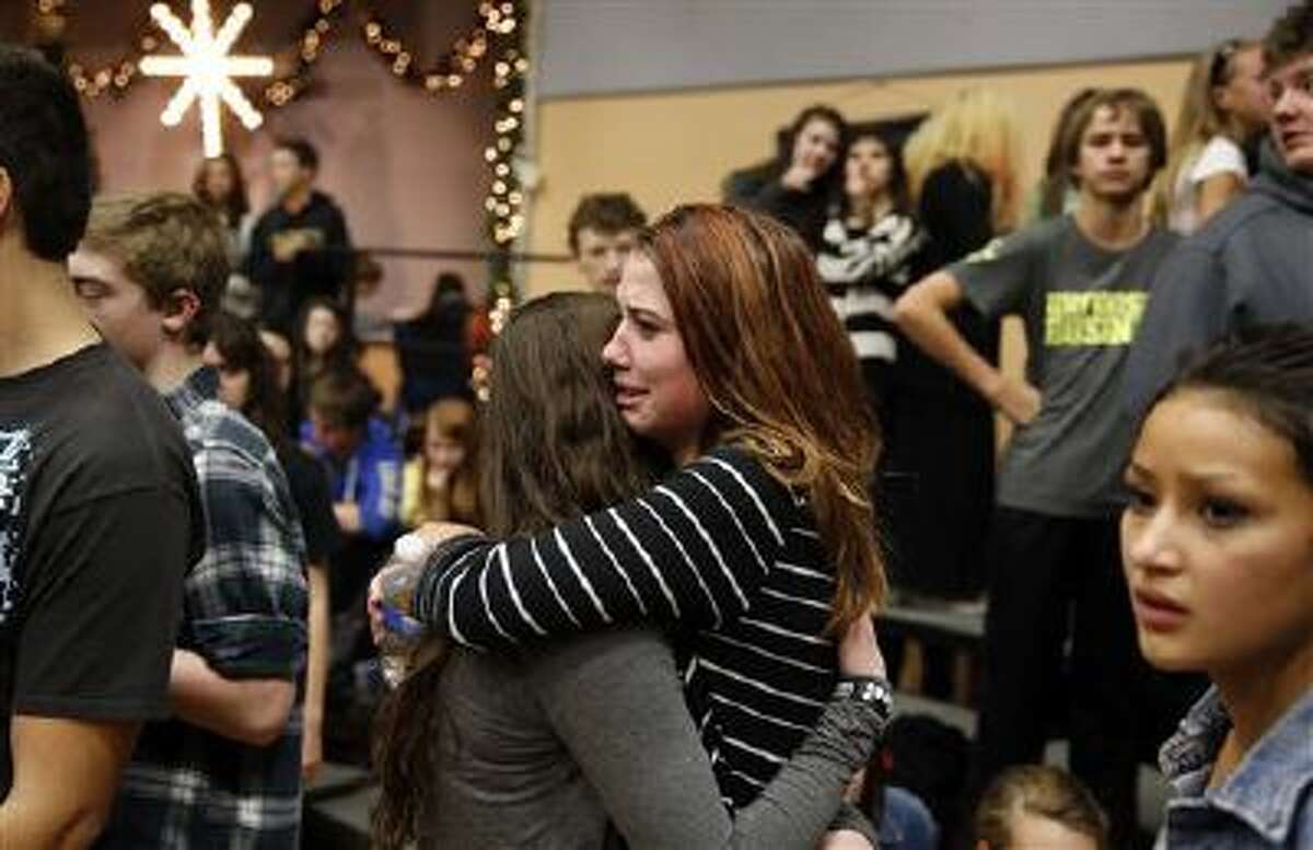 Freshman Allie Zadrow, center right, hugs classmate Liz Reinhardt at a church after a shooting at nearby Arapahoe High School in Centennial, Colo., on Friday. Students were evacuated to the church. Officials said the shooter shot two others at the school, before apparently killing himself. One girl remains in critical condition.