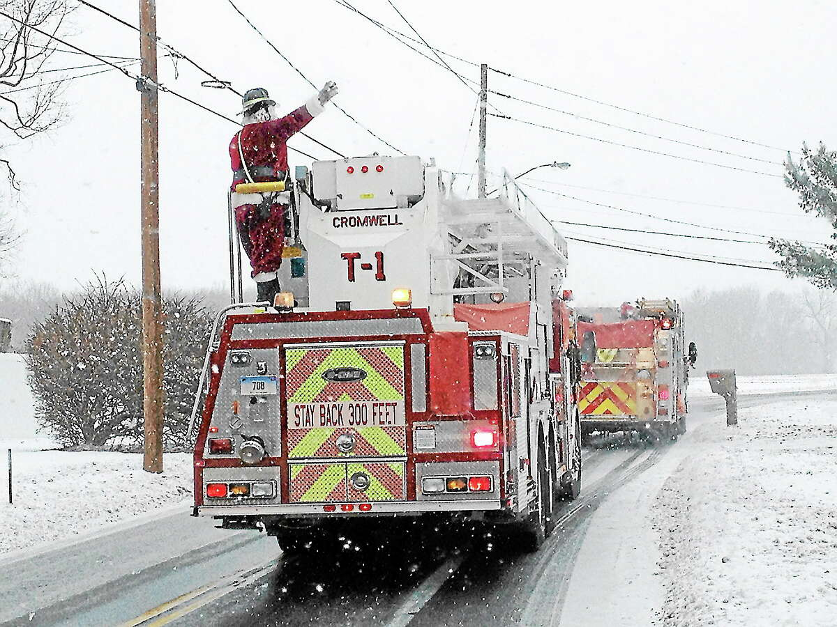 Even as the snow fell, Cromwell firefighters — along with Santa — went through the streets of town to collect donations to help the town's needy residents Saturday.