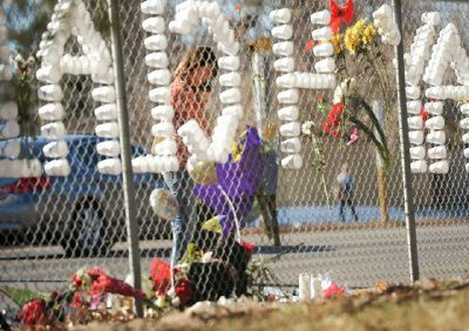 Nicki Winingham and her son Logan, 14, a freshman at Arapahoe High School, pray together at a tribute on a fence near the school in Centennial, Dec. 16, 2013.