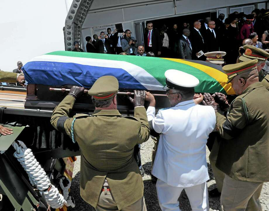 Former South African President Nelson Madela's casket is loaded on a gun carrage following his funeral service in Qunu, South Africa, Sunday, Dec. 15, 2013. AP Photo/Elmond Jiyane Photo: AP / AFP PHOTO/MARCO LONGARI