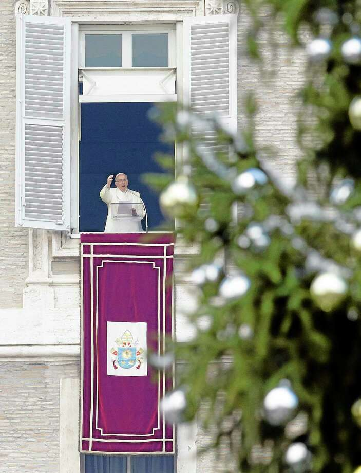 Pope Francis, framed by the adorned branches of a Christmas tree, delivers his message during the Angelus noon prayer from his studio window overlooking St. Peter's Square, at the Vatican, Sunday, Dec. 8, 2013. The pontiff is scheduled to pray in front of the statue of the Virgin Mary in downtown Rome on the occasion of the Immaculate Conception feast later in the afternoon. (AP Photo/Gregorio Borgia) Photo: AP / AP