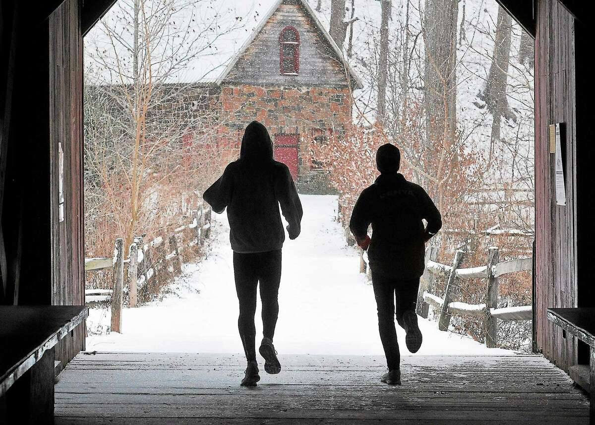 Workers at King Highway Cemetery in Milford clear snow for D.A.R. Runners make their way through the covered bridge at the Eli Whitney Museum during Saturday's snowfall in New Haven.