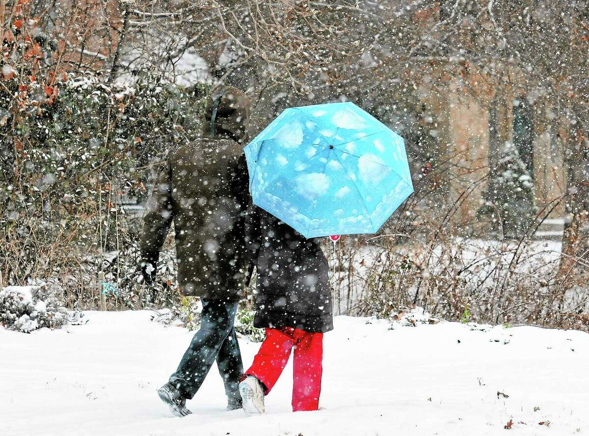 A couple walks along Edgewood Avenue in New Haven during Saturday's storm.