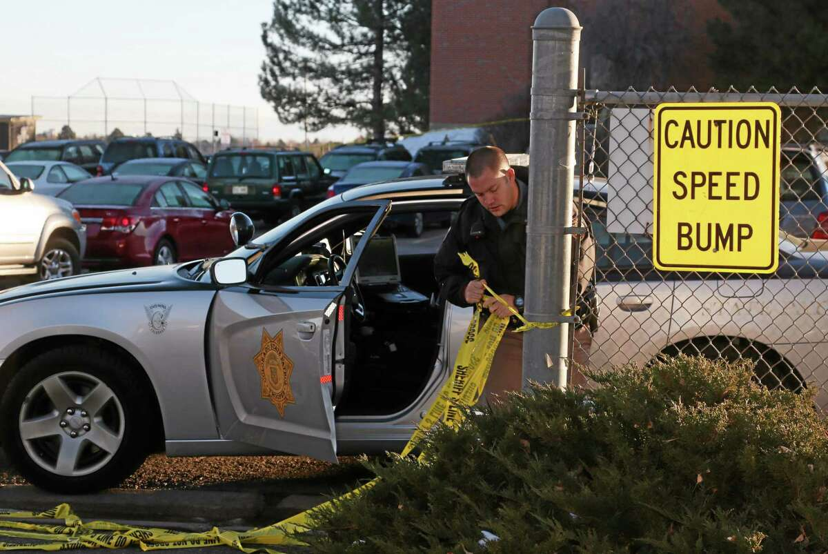 A trooper from the Colorado State Patrol pulls down the safety tape at an entrance to the student parking lot at Arapahoe High School in Centennial, Colo., on Saturday, Dec. 14, 2013. Investigators were working to find out what motivated a teenage gunman to enter his suburban Denver high school armed with a shotgun looking for a specific teacher a day earlier. The 18-year-old shooter critically wounded a 15-year-old student and was later found dead in the school, apparently of a self-inflicted gunshot wound. (AP Photo/David Zalubowski) (AP Photo/David Zalubowski)