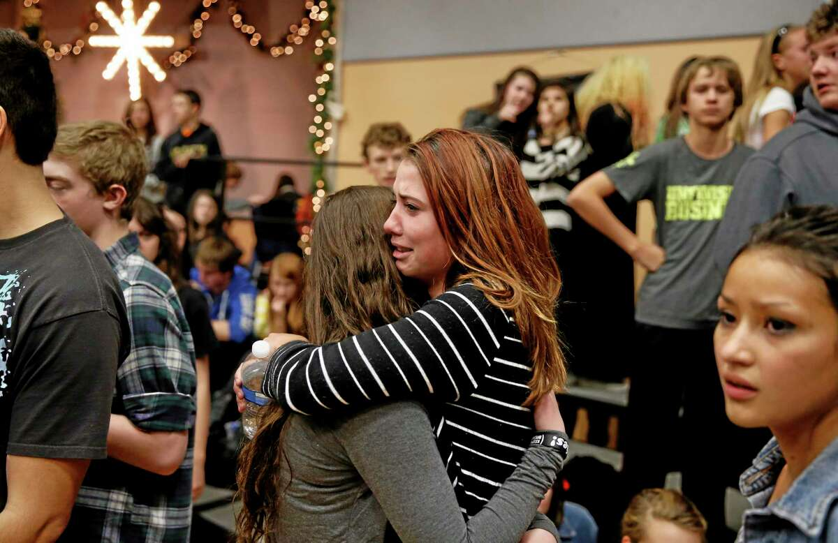 Freshman Allie Zadrow, center right, hugs classmate Liz Reinhardt at a church after a shooting at nearby Arapahoe High School in Centennial, Colo., on Friday, Dec. 13, 2013. Students from the school were evacuated to the church. Arapahoe County Sheriff Grayson Robinson said the shooter shot two others at the school, before apparently killing himself. (AP Photo/Brennan Linsley)