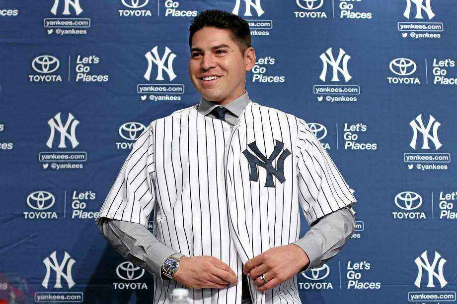 Jacoby Ellsbury buttons up his jersey after being introduced during a news conference Friday at Yankee Stadium in the Bronx. The former Red Sox outfielder agreed to a $153 million, seven-year contract. Photo: John Minchillo — The Associated Press  / FR170537 AP