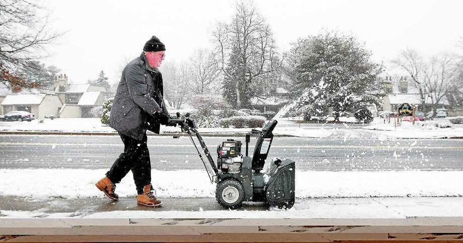 Dan Thewlis clears the sidewalk Dec. 10 in front of Island View Senior Housing in Milford. Photo: Arnold Gold — New Haven Register