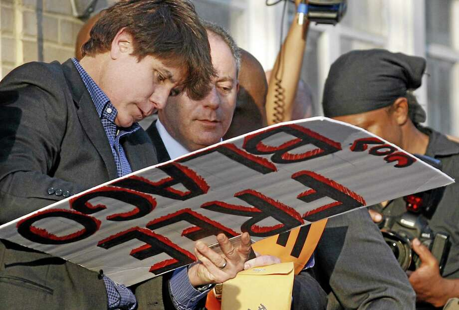 FILE - This March 14, 2012 file photo shows former Illinois Gov. Rod Blagojevich autographing a 'Free Gov. Blago' sign for one of  his supporters outside his home in Chicago the day before The 55-year-old Democrat was due to report to a prison in Colorado to begin serving a 14-year sentence on corruption charges. The Imprisoned ex-Gov. gets what's likely his last chance to win his freedom as his appeal goes before  the 7th U.S. Circuit Court of Appeals for oral arguments Friday, Dec. 12, 2013 in Chicago. (AP Photo/M. Spencer Green, File) Photo: AP / AP